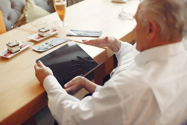 Elegante oude paar in een café met behulp van een tablet