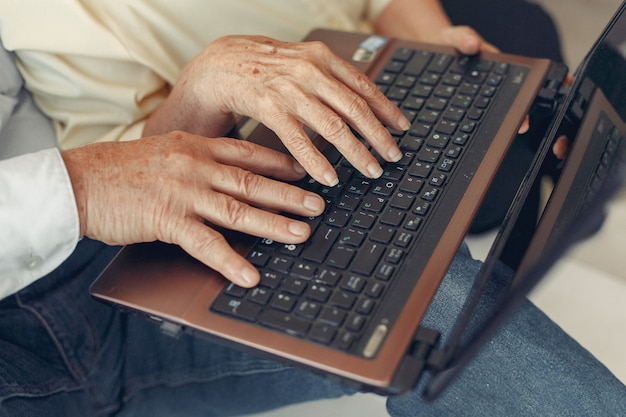 Elegante oude paar om thuis te zitten en een laptop te gebruiken