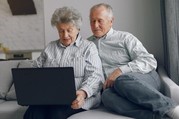 Elegante oude paar om thuis te zitten en het gebruik van een laptop