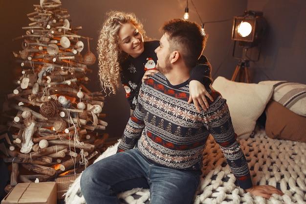 Elegante paar om thuis te zitten in de buurt van de kerstboom
