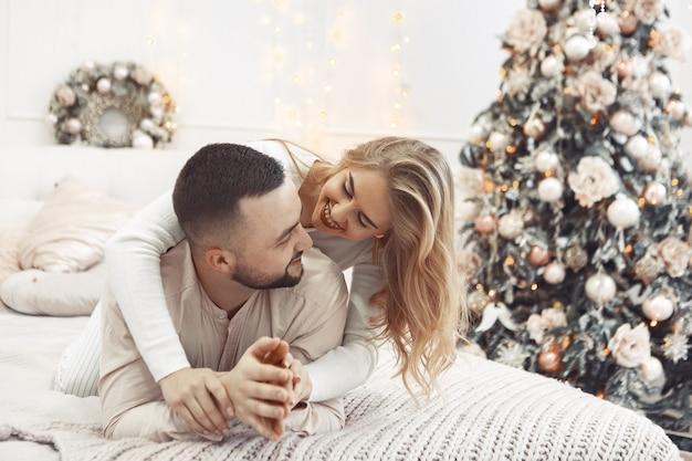 Elegante paar zittend op een bed in een kerstversiering