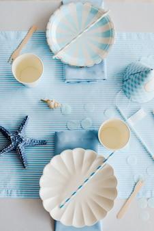 Elegante papieren borden op voorbereide verjaardagstafel met voor kinderen of meisjesfeest in hemelsblauwe en witte kleuren. baby jongen douche. close-up, bovenaanzicht