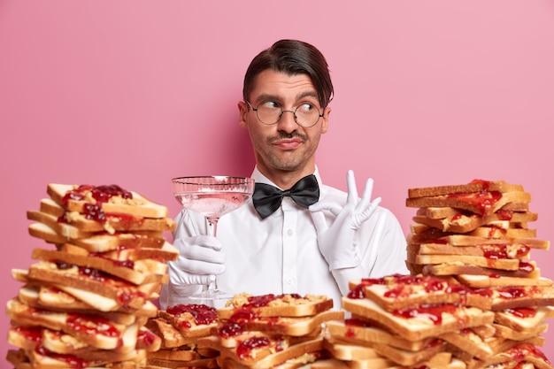 Elegante peinzende ober raakt vlinderdas aan, gekleed in sneeuwwit uniform, stelt voor om een nieuwe cocktail te degusteren, kijkt bedachtzaam opzij, poseert naast een stapel heerlijke toastbroodjes. barman op het werk