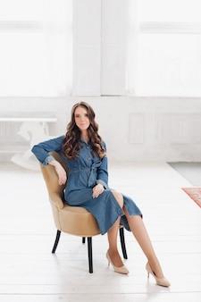 Elegante prachtige brunette vrouw in denim jurk en hakken het lezen van een tijdschrift