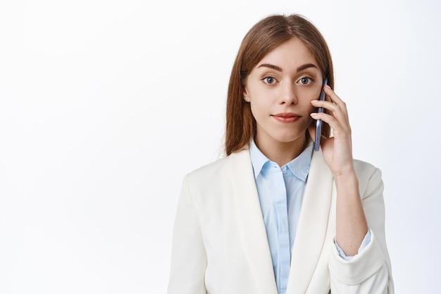Elegante professionele vrouw praat op mobiele telefoon, kijkt zelfverzekerd en vastberaden naar voren, belt op het werk, staat over een witte muur