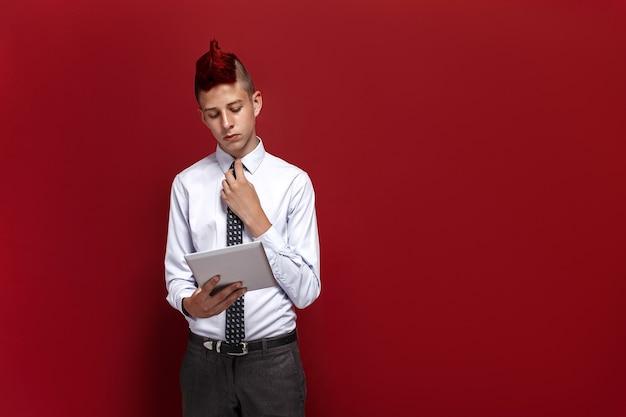Elegante punk met tablet tegen rode ruimte