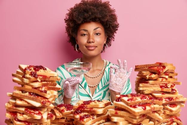 Elegante retro vrouw degusteert, maakt perfecte teken, gekleed in een stijlvolle jurk met sieraden en kanten handschoenen, wordt op avondfeest in luxe restaurant, heeft de verleiding om heerlijke toast te eten