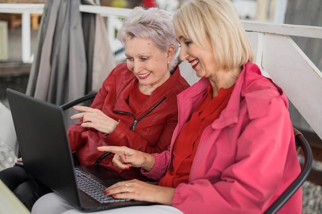 Elegante rijpe vrouwen die laptop met behulp van