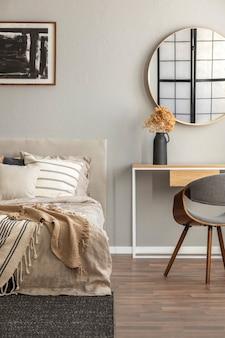 Elegante ronde spiegel in houten frame boven chique consoletafel met bloemen in vaas trendy slaapkamer