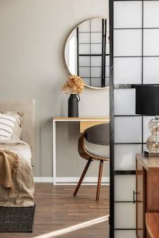 Elegante ronde spiegel in houten frame boven fancy consoletafel met bloemen in vaas in trendy