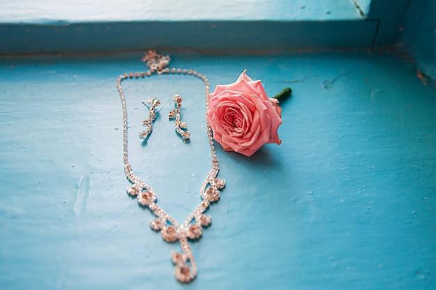 Elegante roos met ketting en oorbellen op een blauwe