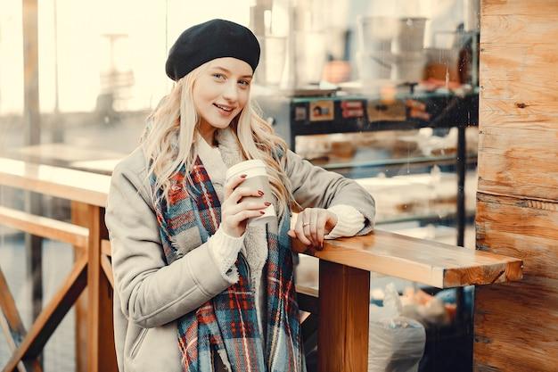 Elegante schattige blonde in een herfst stad