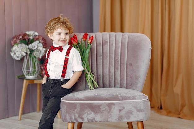 Elegante schattige kleine jongen met boeket van tulp