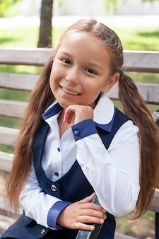 Elegante schoolmeisje-meisje wandelen in het park, leren concept. schooluniform. 1 september