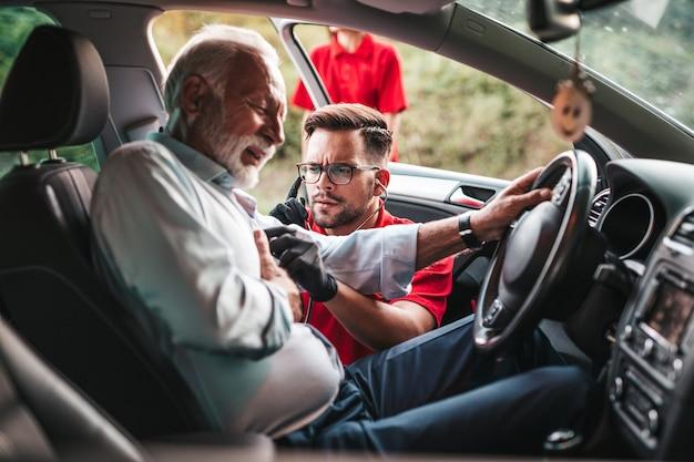 Elegante senior man met symptomen van een hartaanval op de weg. hulpverleners van de medische dienst proberen hem te helpen.