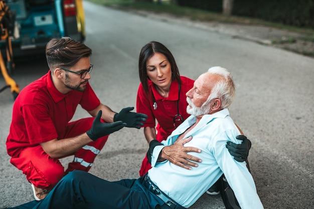 Elegante senior man met symptomen van een hartaanval zittend op de weg medische hulpdiensten die hem proberen te helpen. rijhulpdienst.