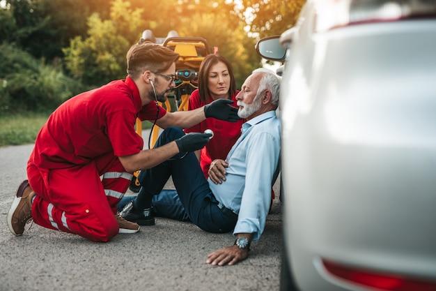 Elegante senior man met symptomen van een hartaanval zittend op de weg medische hulpdiensten die hem proberen te helpen.
