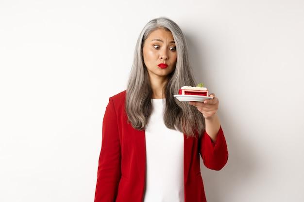 Elegante senior vrouw in rode blazer wil een hap van zoete cake, kijkend met verleid gezicht naar het toetje, staande over een witte muur.