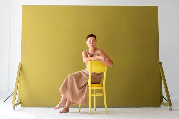 Elegante senior vrouw zittend op een stoel
