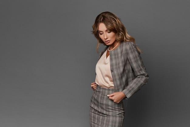 Elegante sensuele zakenvrouw met officiële make-up en kapsel in modieus geruit pak poseren op een grijze achtergrond, geïsoleerd. mooi verleidelijk modelmeisje in formele kleding op grijze achtergrond