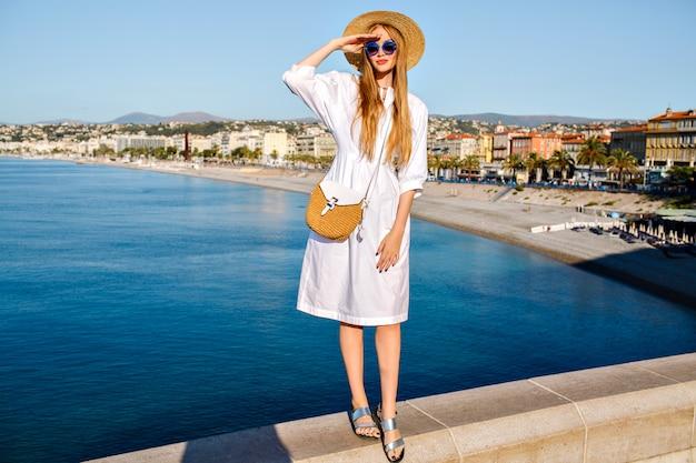 Elegante sensuele zalige blonde vrouw poseren voor een prachtig uitzicht op het mooie strand van de franse rivièra