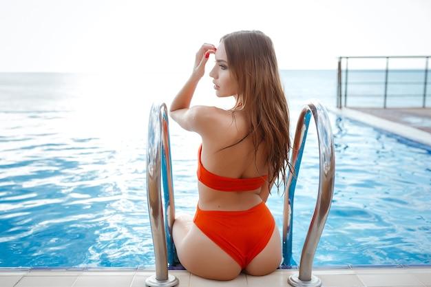 Elegante sexy vrouw in de oranje bikini op het zongebruinde slanke en welgevormde lichaam is poseren bij het zwembad