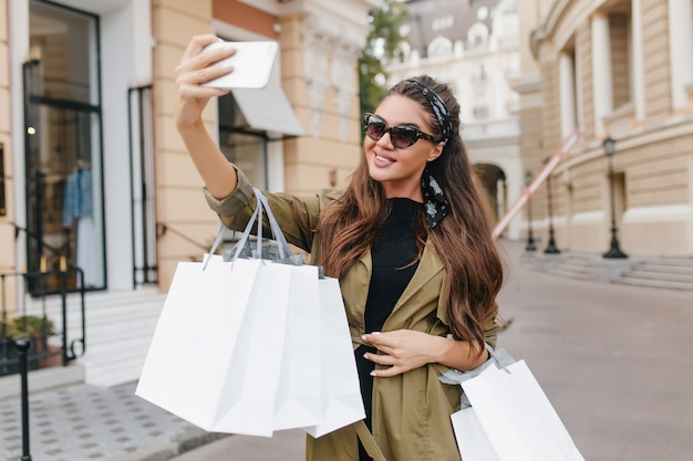Elegante shopaholic vrouw selfie met gelukkige glimlach houden papieren zakken