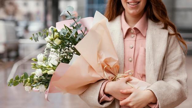 Elegante smiley vrouw met boeket bloemen buiten