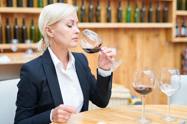 Elegante sommelier zittend aan tafel in de kelder en cabernet proeven van wijnglas om de kwaliteit ervan te controleren