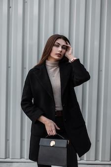 Elegante stedelijke model jonge vrouw met lang haar in shirt in luxe modieuze zwarte jas met lederen handtas poseren in de buurt van metalen zilveren muur op straat. mooi meisjesmodel. leuke trendy dame.