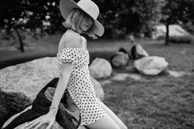 Elegante stijlvolle blonde kort haar meisje in hoed die zich voordeed op de stenen in het park