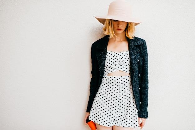 Elegante stijlvolle blonde kort haar meisje in hoed en jurk poseren met koffie op witte achtergrond