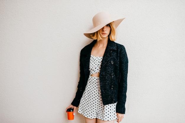 Elegante stijlvolle blonde kort haar meisje in hoed en jurk poseren met koffie over wit