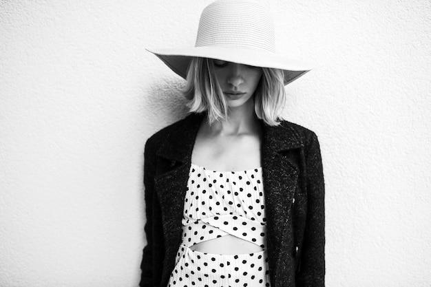 Elegante stijlvolle blonde kort haar meisje in hoed en jurk poseren op muur achtergrond