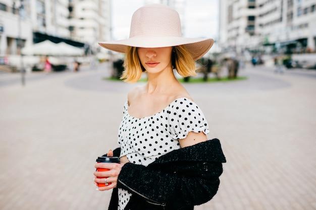 Elegante stijlvolle blonde kort haar meisje in hoed en jurk poseren op straat achtergrond