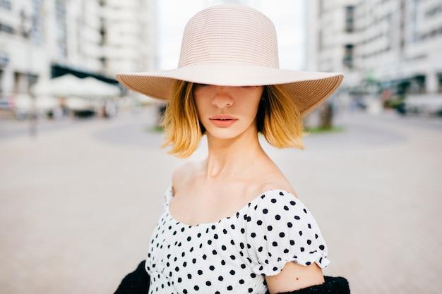 Elegante stijlvolle blonde kort haar meisje in hoed en jurk poseren over straat