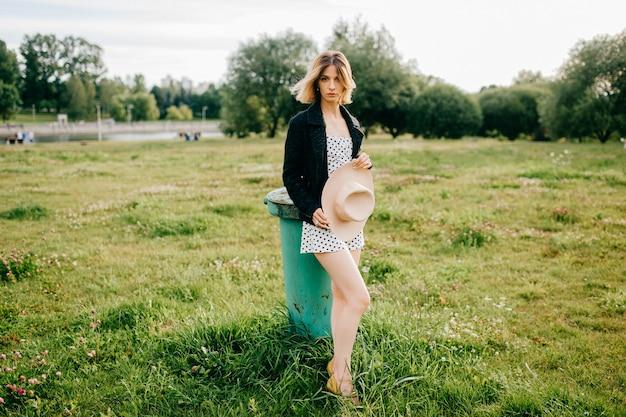 Elegante stijlvolle blonde kort haar meisje poseren met hoed in het veld