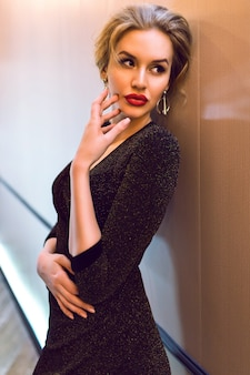 Elegante stijlvolle dame draagt lange sprankelende avondjurk poseren in hotel gang, film effect, afgezwakt zachte kleuren, luxe leven.