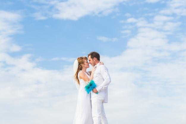 Elegante stijlvolle gelukkige bruid en prachtige bruidegom op de achtergrond van de blauwe hemel