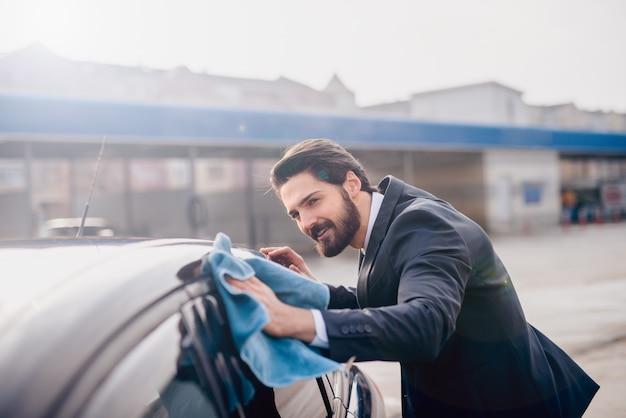 Elegante stijlvolle jonge bebaarde man in pak achterruit van de auto met een blauwe microfiber doek schoonmaken.