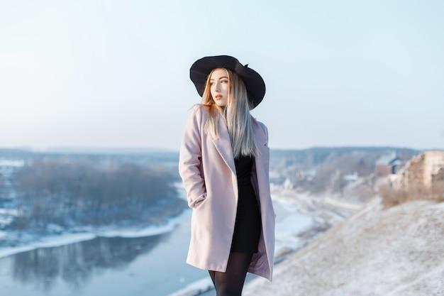 Elegante stijlvolle jonge vrouw in een roze stijlvolle jas in een chique hoed in een zwarte gebreide jurk staat op een berg aan de rivier. stijlvol meisje geniet van het winterlandschap.