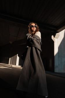 Elegante, stijlvolle, krullende jonge modelvrouw met zonnebril in een mode-lange jas op de achtergrond van betonnen stedelijke architectuur in zonlicht en schaduw