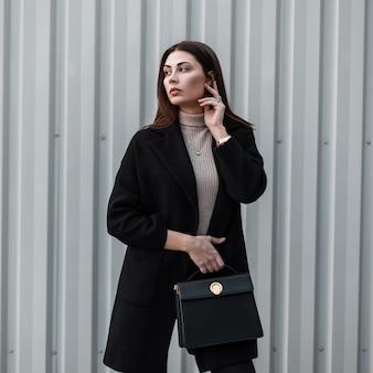 Elegante stijlvolle model jonge vrouw met lang haar in shirt in luxe modieuze zwarte jas met lederen handtas poseren in de buurt van metalen zilveren muur op straat. mooi meisjesmodel. leuke trendy dame.