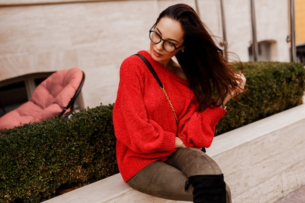 Elegante succesvolle brunette vrouw poseren buiten in trendy lente outfit. modieuze laarzen, rode gebreide trui. oude europese stad.