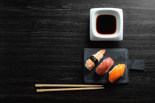 Elegante sushi op houten tafel. wat nigiri, met sojasaus en eetstokje
