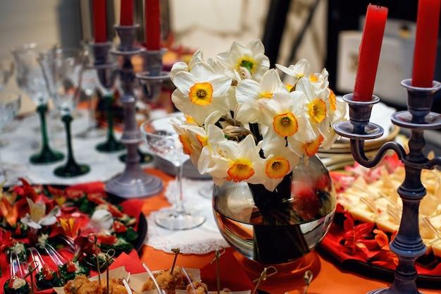 Elegante vaas met boeket narcissen om de eettafel te versieren mooie feestelijke tafelsetting