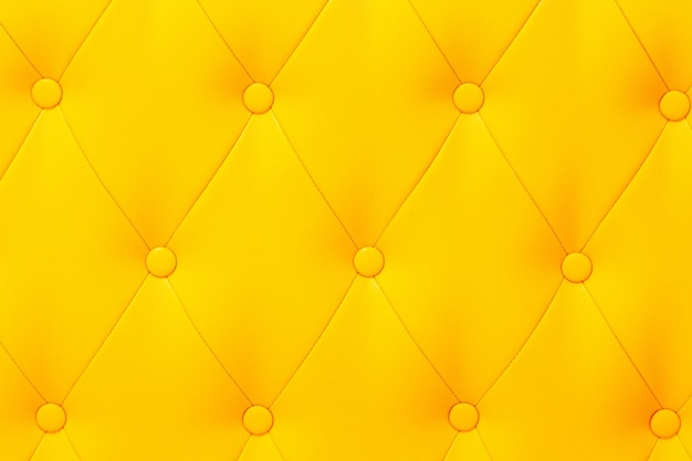 Elegante verzadigde glanzende gele leertextuur van bankstoel.