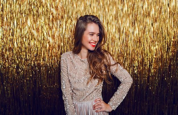 Elegante vierende vrouw met verrassingsgezicht dat zich over gouden fonkeling bevindt