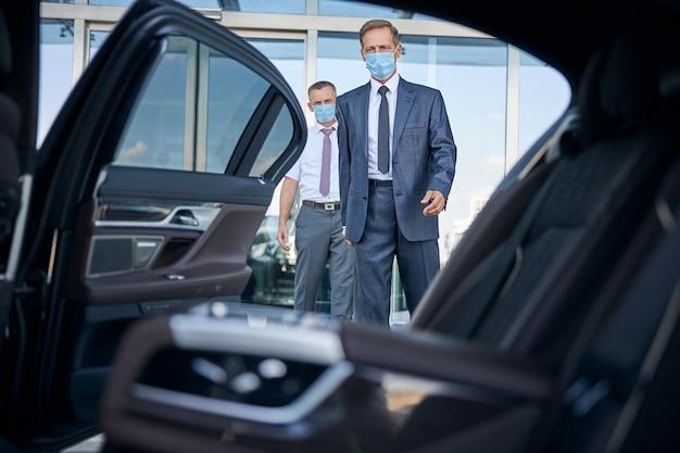 Elegante volwassen man met steriel masker stapt na aankomst in de auto terwijl de chauffeur de koffer vasthoudt