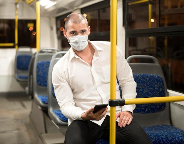 Elegante volwassen mannelijke bus rijden met medische masker
